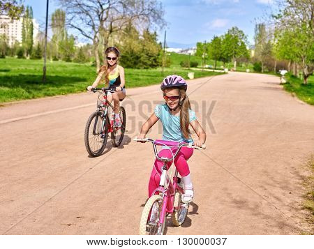 Bikes bicycling girl. Girl rides bicycle. Girl in cycling riding on bicycle lane . Children outrace one another . Cyclist looking at camera.