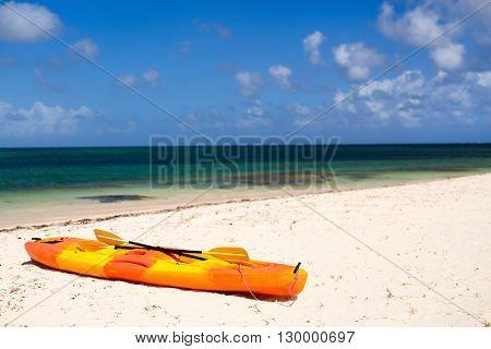 Colorful orange kayak at tropical white sand beach in Caribbean