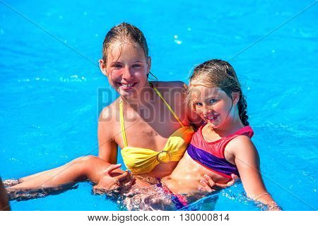 Two children in swimming pool . Children hugging. Summer holiday.  Outdoor. Children  activities lifestyle.