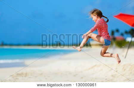Happy little girl at beach having a lot of fun on summer vacation