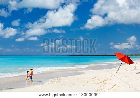 Kids at idyllic tropical beach with white sand, turquoise ocean water and blue sky at deserted island in Caribbean