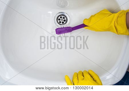 Woman's hands in yellow gloves cleaning a sink with brush. Cleaning concept.