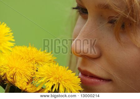 Beautiful young blond woman (girl) in a field enjoying the sun and smelling the yellow flowers