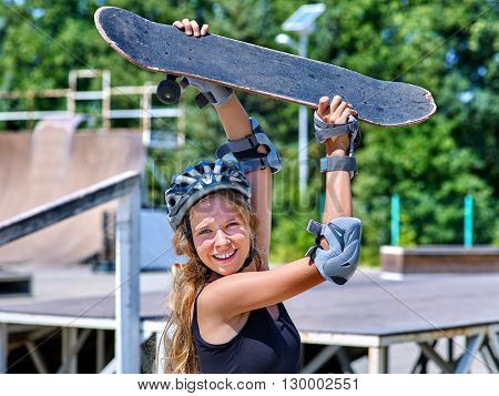 Teen skateboarding his skateboard outdoor. Girl holding  skate on his head. Skateboard is extreme sport.