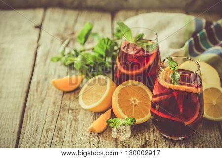 Sangria and ingredients in glasses, copy space, toned