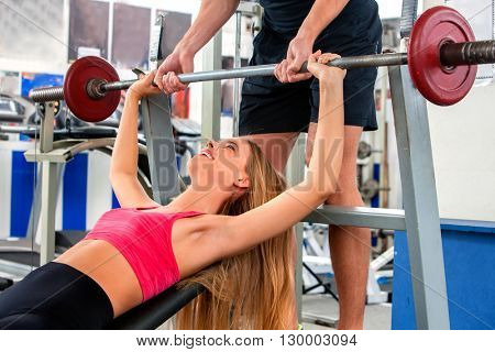 Woman working with barbell and her arms and chest at gym. She lifting barbell. Man backs her up while she taking exercises with barbell .