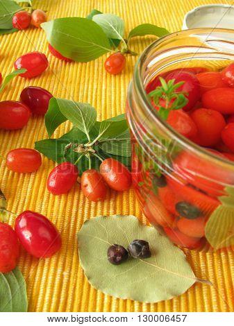 Cornelian cherries in vinegar marinade in jar