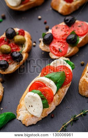 Italian bruschetta with tomatoes, mozzarella cheese and herbs on a slate background