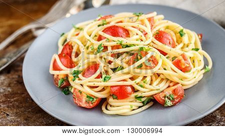 Spaghetti pasta with cherry tomatoes and parsley on rustric background