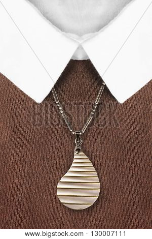 Golden pendant on a chain over brown pullover closeup