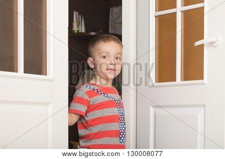 Happy smiling boy looking out the door ajar