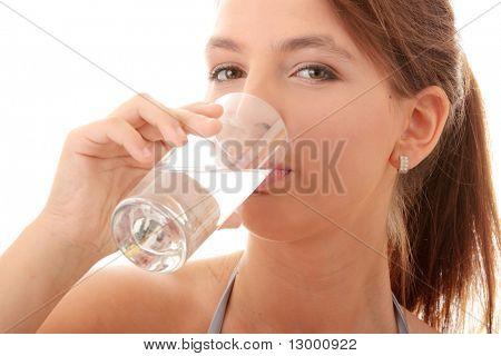 Joven, beber agua fría de vidrio - aislado en blanco