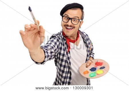Joyful young painter holding a color palette and painting with paintbrush isolated on white background