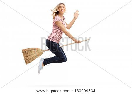 Woman flying on a broom and waving with her hand towards the camera isolated on white background