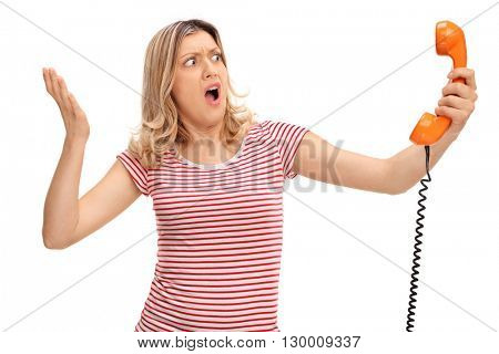 Angry woman holding an orange telephone speaker isolated on white background