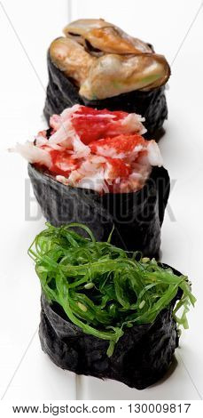 Various Japanese Sushi Gunkan Rolled Up in Nigiri with Seaweed Shrimps and Mussels in Sauce closeup on Plank White background. Focus on Foreground