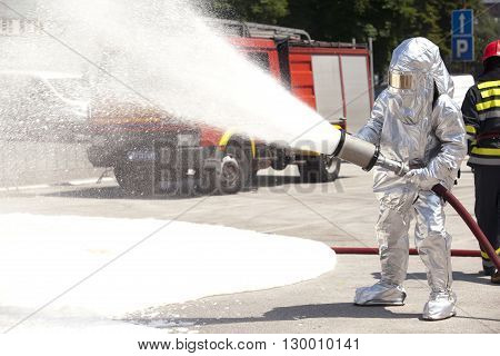 Firefighter training. Firefighter in action spraying fire with fire hose