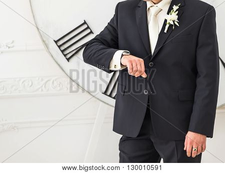 young business man  looking at watch over big clock background