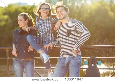 Friendship leisure summer technology and people concept - smiling friends having fun outdoors