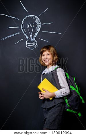 Educational concept. Smiling schoolgirl standing with books and school bag by a blackboard. Copy space.