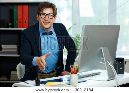 Modern young business man with arm extended to handshake