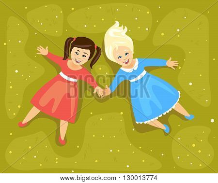 Friendship. Girls lying on a meadow and holding hands. Top view
