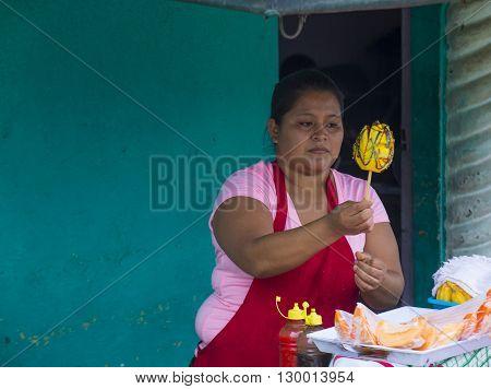 PANCHIMALCO EL SALVADOR - MAY 08 : A Salvadoran woman sells mango on a stick during the Flower & Palm Festival in Panchimalco El Salvador on May 08 2016