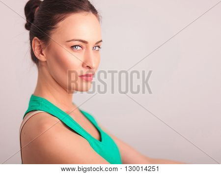 closeup portrait of a beautiful serious woman in green undershirt looking at hte camera