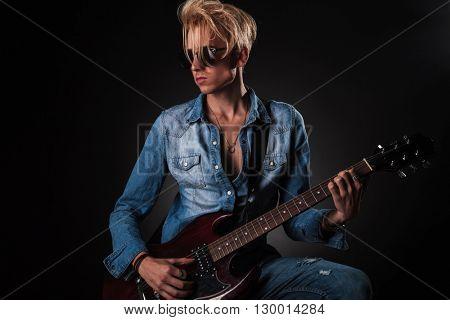 passionate guitarist playing his electric guitar in studio