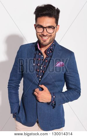 confident young man in suit laughing in studio while holding coat's button