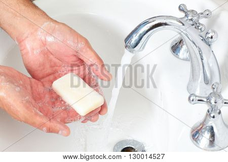 Man washing hands with soap and water.