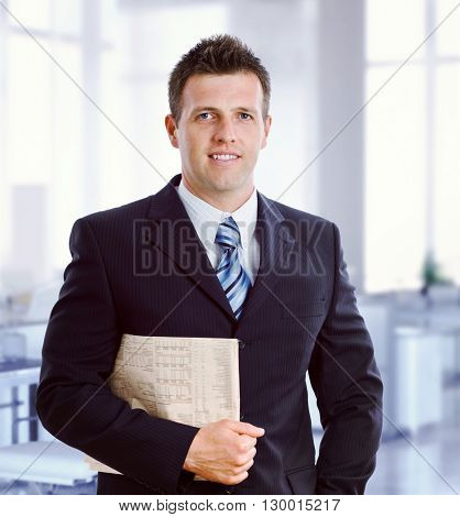Young caucasian formal broker with newspaper under arm at business office. Smiling, standing, looking at camera, suit and tie.