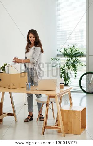 Pretty young woman unpacking in new office
