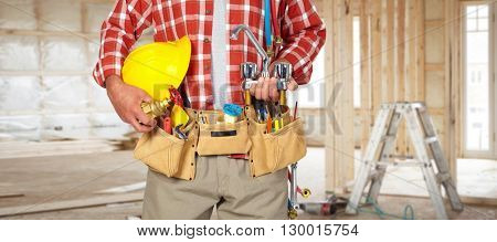 Plumber hands with helmet and water tap.