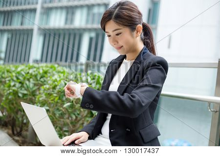 Businesswoman working on laptop computer and check the time on smart watch
