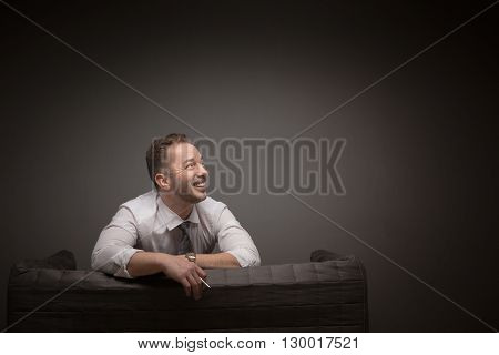 Smilng businessman sitting on sofa and looking away in studio. Happy young man without jacket resting after hard-working day.