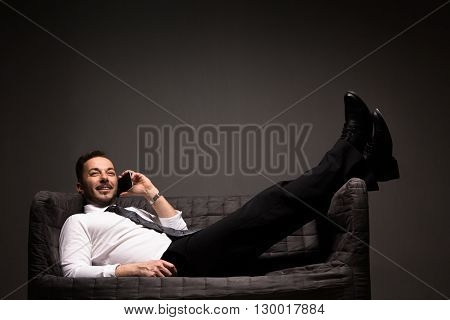 Studio shot of handsome businessman speaking over mobile or smart phone while lying on comfortable sofa after hard-working day.