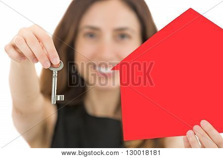 Attractive business woman showing a key for a home for sale. Focus on the key. Isolated onwhite background.