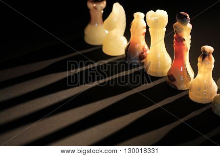 Set of chess pieces made from onyx against light on dark background