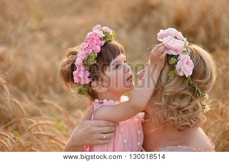 The daughter and mother look at each other, the daughter straightens the wreath of roses on her head