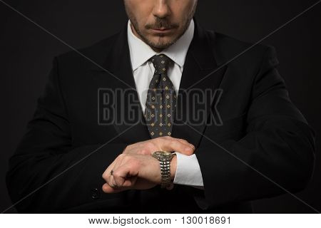 Closeup portrait of businessman checking time on his hand. Serious man looking at his watch not to be late for work. Studio shot.