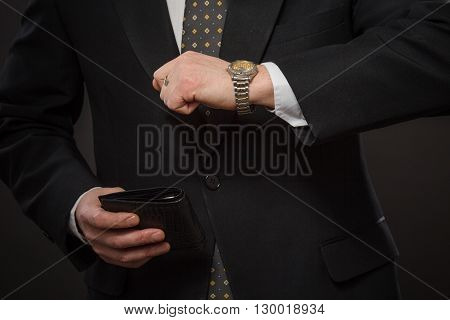 Closeup portrait of businessman with expensive black wallet. Man in black suit going to company, enterprise or firm for business meeting.