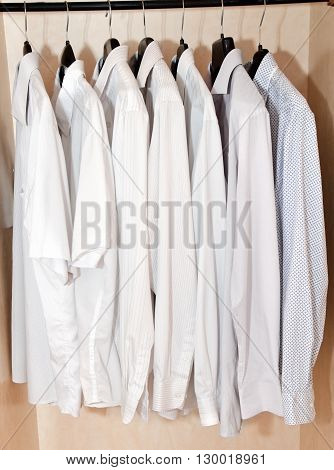 Men's shirts on hangers in the wardrobe