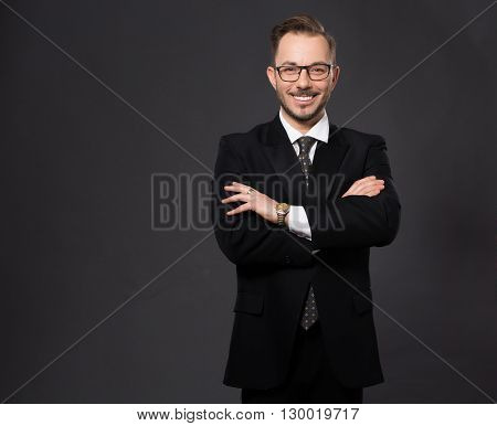 Portrait of businessman happy smiling and posing with his ars crossed or folded in studio. Real executive or corporate officer isolated on grey background.