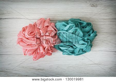 Pink and turquoise washcloths on the wooden background. Body care. Toileting theme. Product photo.