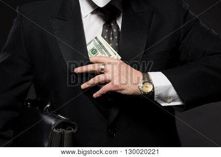 Businessman with money in studio. Currency bribing. Businessman hiding money in jacket pocket. Corruption and fraud concepts.