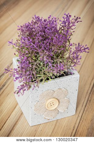 Small decorative potted plant on the wooden background. Home decoration. Beautiful house plant. Artificial flower.
