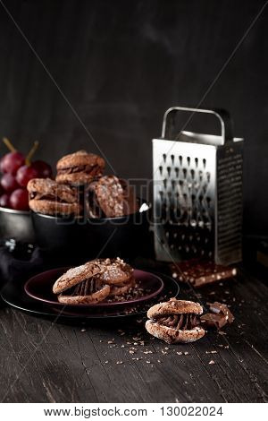 Italian maroni cookies on the plate and bowl with grapes cloth notebook on dark old wooden background