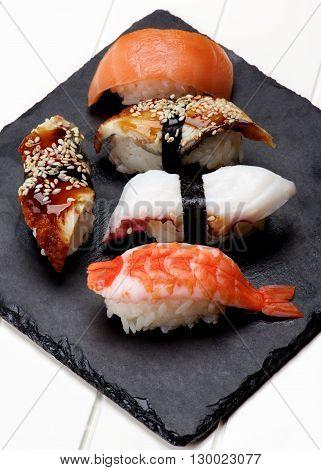 Various Sashimi Sushi with Shrimp Octopus Smoked Eel and Salmon on Stone Plate closeup on White Plank background
