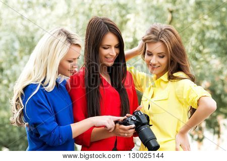 Three beautiful women having a photosession in the park with new dslr camera.